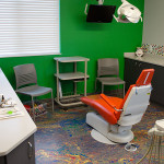 image of pediatric dental room with green walls and orange dentist chair